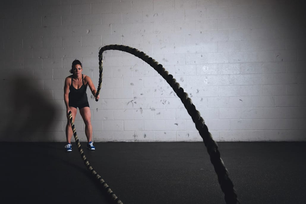 Woman uses battle ropes in a gym.