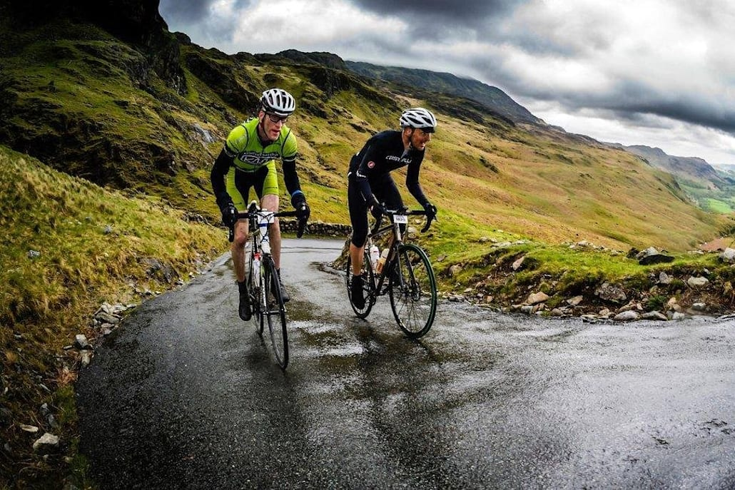 Two cyclists battle up a mountain.