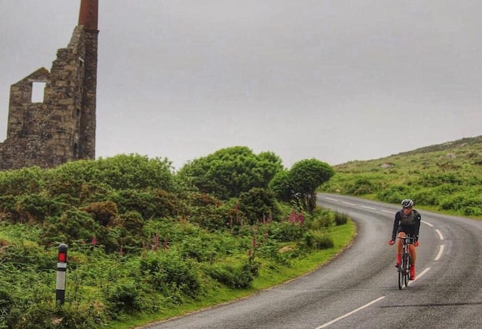 A cyclist descends a rural hill in the UK.