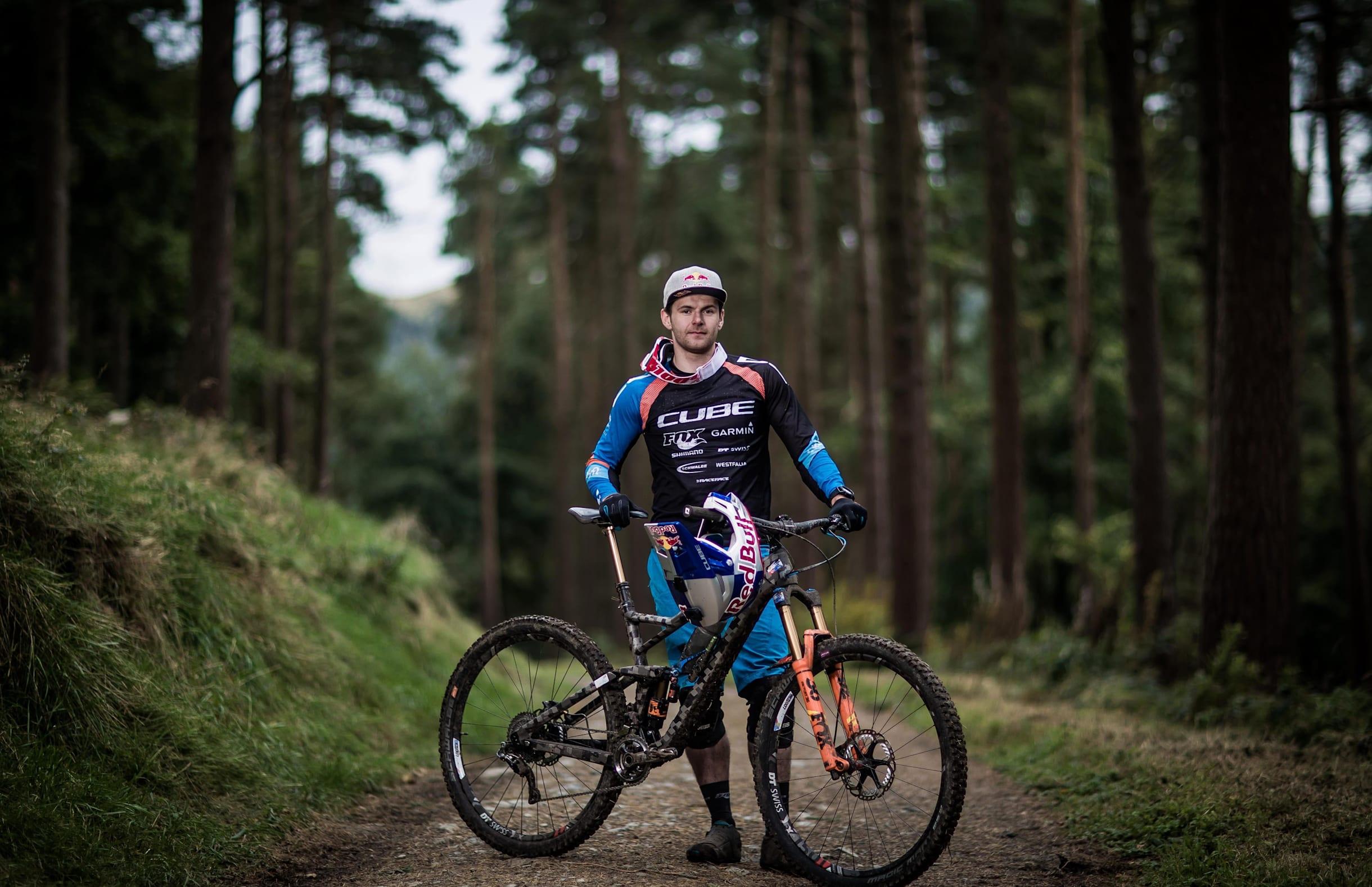 El rider irlandés Greg Gallaghan posa junto a su bici de enduro.