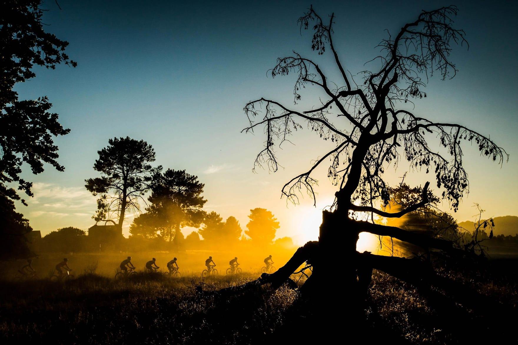 Fahrer im frühen Morgenlicht beim Absa Cape Epic Mountainbike-Etappenrennen