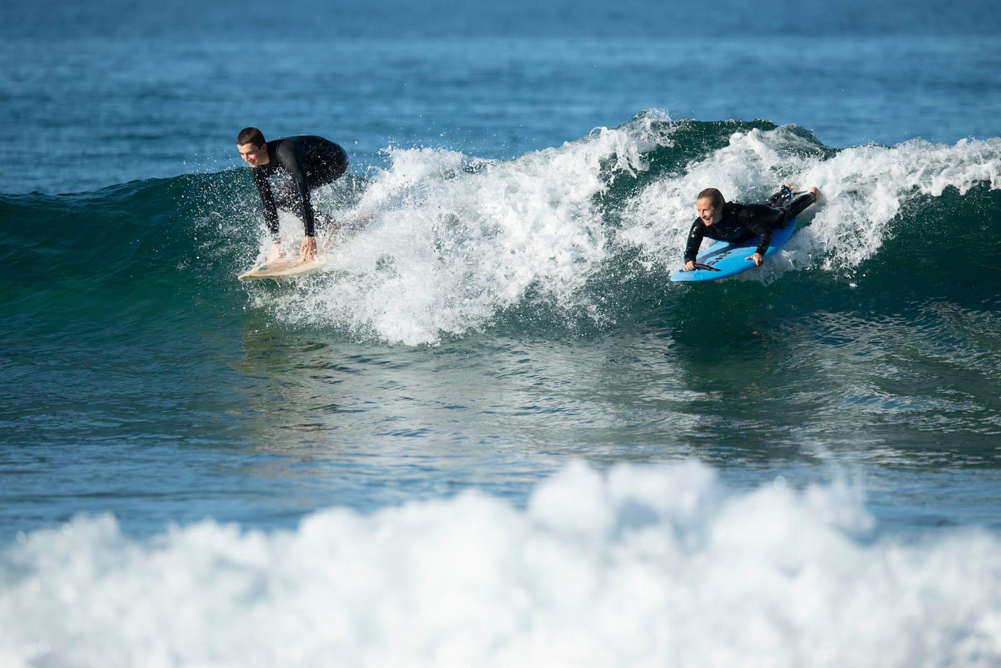 Sam surfs with her son, Noah, at Bilgola.